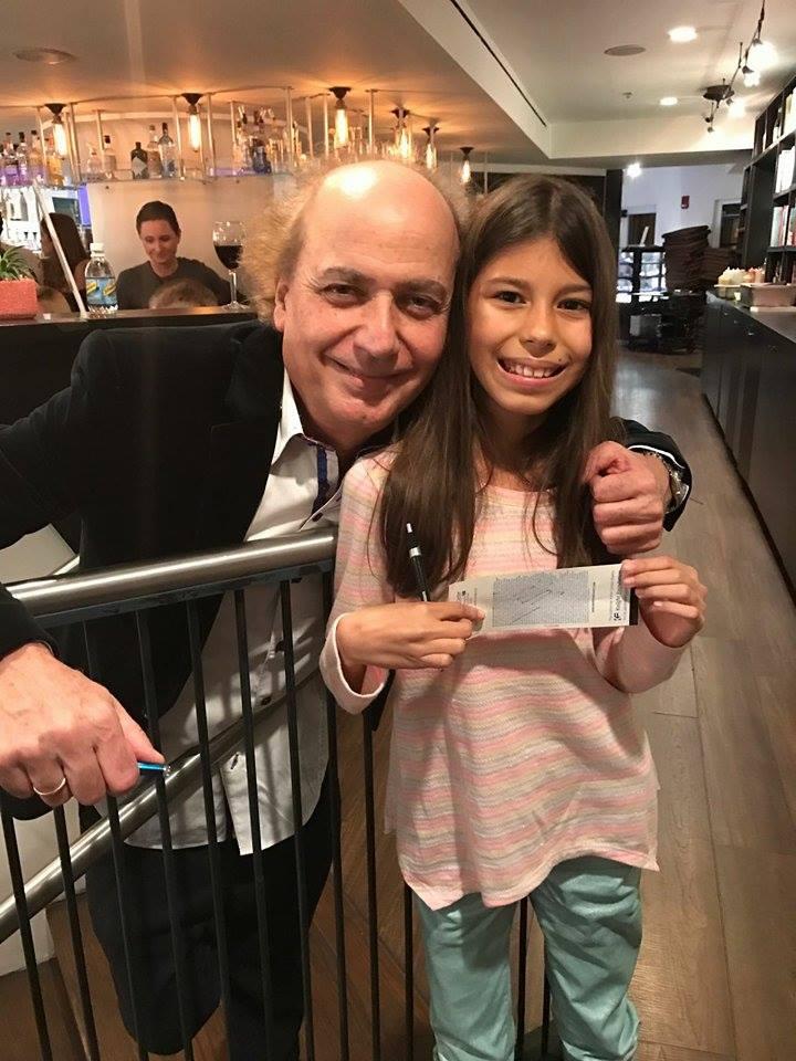 Fabiana, una de las niñas venezolanas que asistió al concierto, con el Maestro Eduardo Marturet quien le autografió la entrada